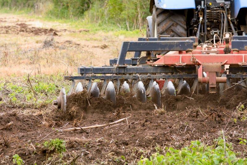 使用拖拉机的农夫耕领域 库存图片