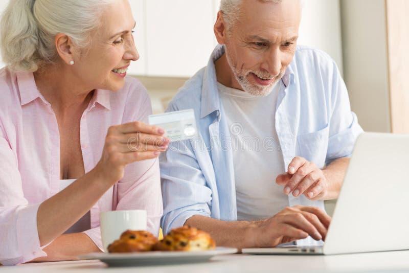 使用拿着信用卡的膝上型计算机的愉快的成熟爱恋的夫妇家庭 免版税库存图片