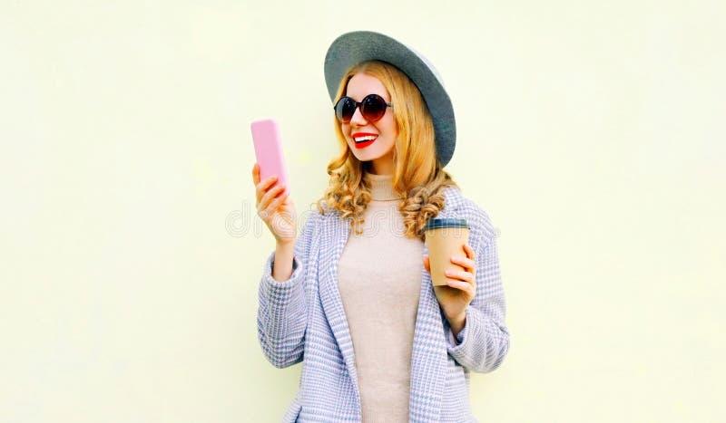 使用拿着咖啡杯,卷发,佩带的圆的帽子,在背景的外套夹克的电话的画象年轻女人 免版税图库摄影