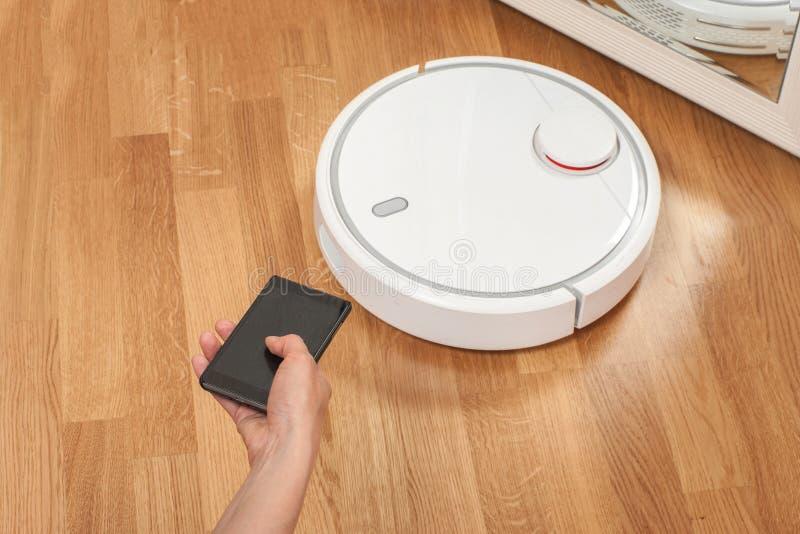 使用控制的机动性的妇女的手白色机器人吸尘器 现代聪明的清洁工艺 免版税库存图片