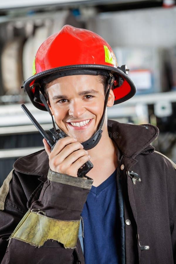 使用携带无线电话的微笑的消防员 免版税库存照片
