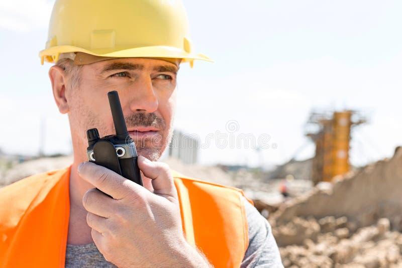 使用携带无线电话的确信的监督员在建造场所 免版税库存图片
