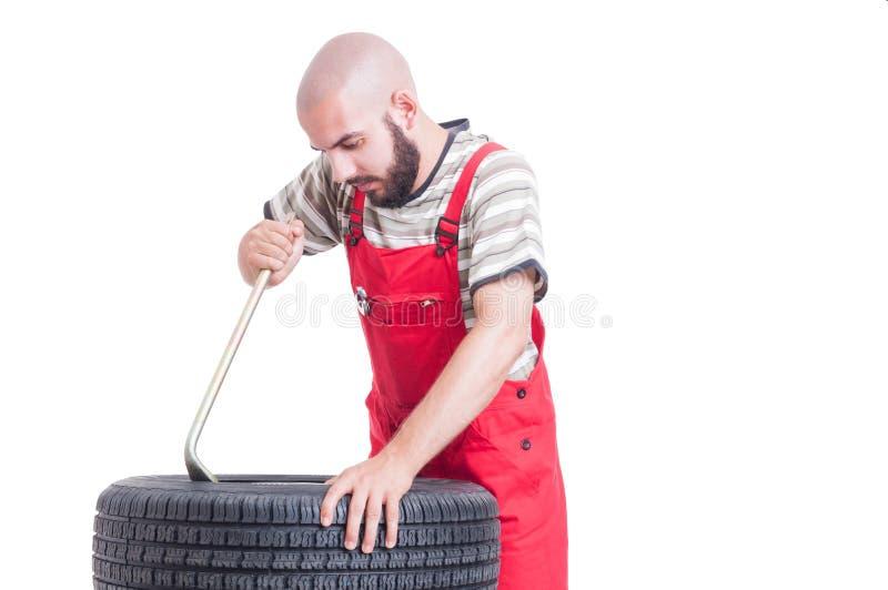 使用撬杠的技工改变的轮胎 库存照片