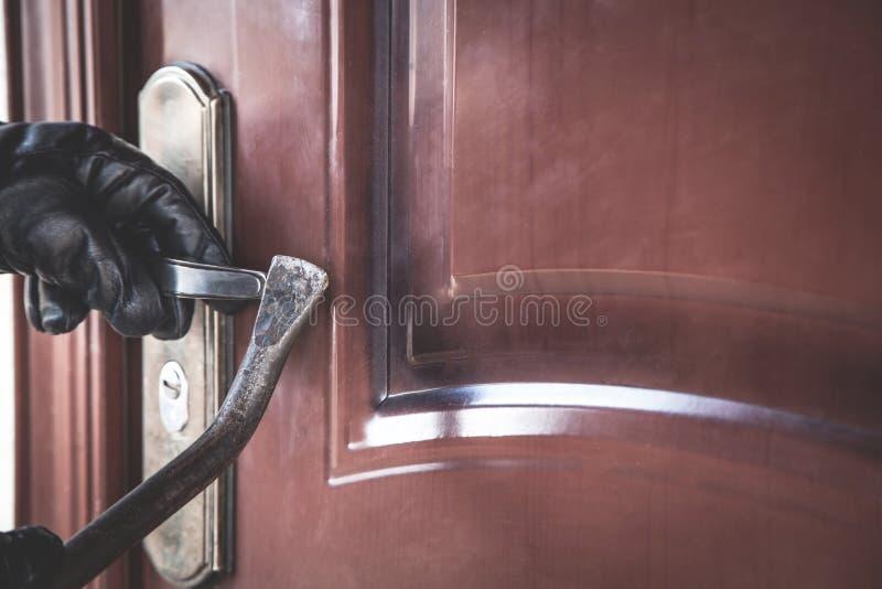 使用撬杠,设法的夜贼打开门 免版税库存照片