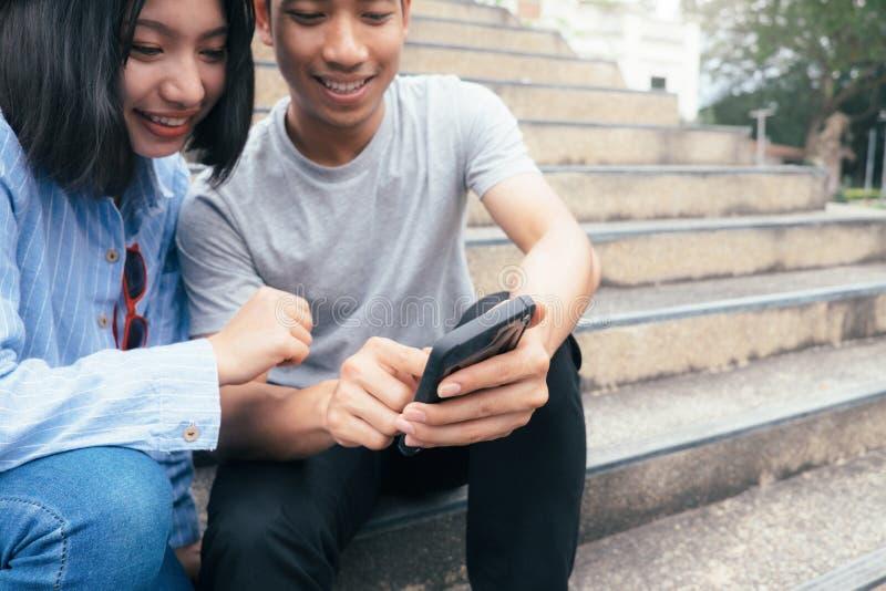 使用数字式手机的少年学生 免版税库存照片