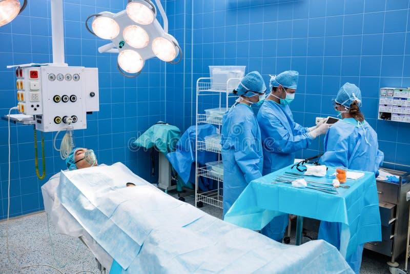 使用数字式片剂和患者的外科医生说谎在操作供住宿 免版税库存照片