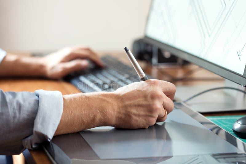 使用数字式片剂和计算机的图表设计师 免版税库存照片