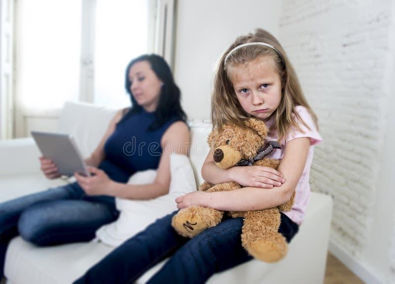 使用数字式片剂垫的年轻互联网上瘾者母亲忽略小哀伤的女儿 库存照片