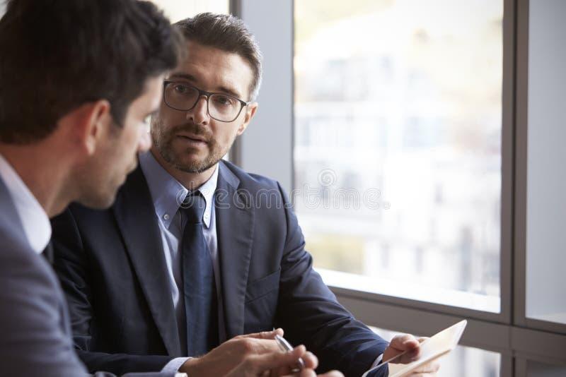 使用数字式片剂的两个商人在办公室会议 免版税库存照片