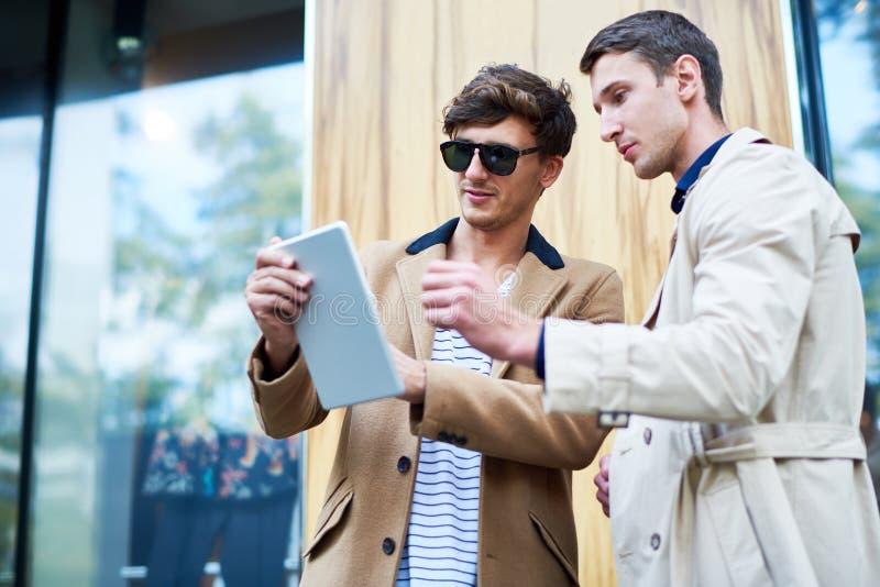 使用数字式片剂的两青年人在街道 免版税库存图片