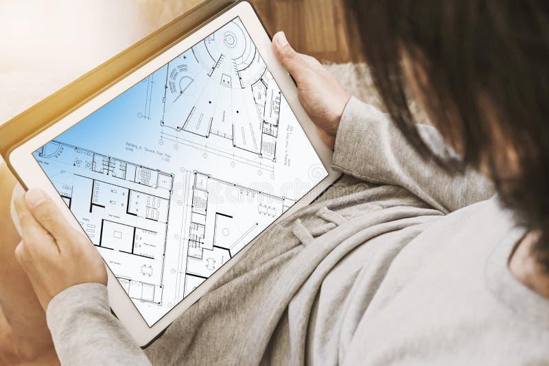 使用数字式片剂的亚裔人在客厅,有在屏幕上的建筑布局计划的 库存照片