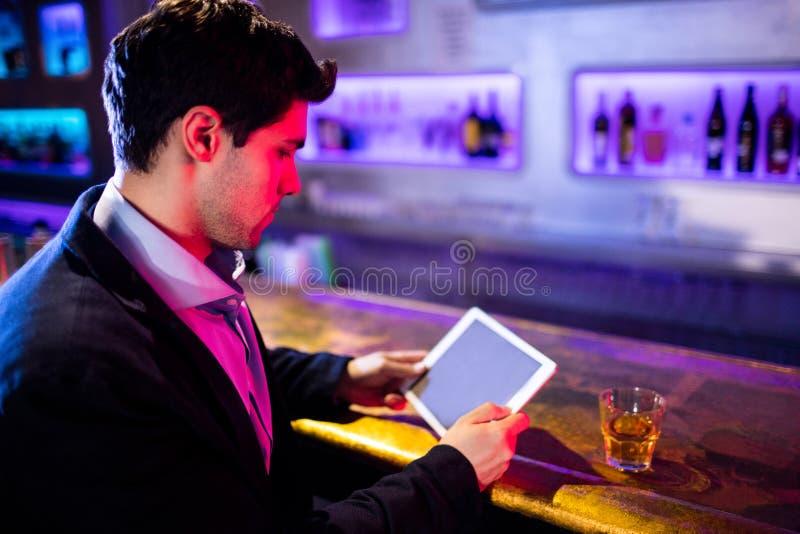 使用数字式片剂的人,当食用威士忌酒在酒吧柜台时 库存照片