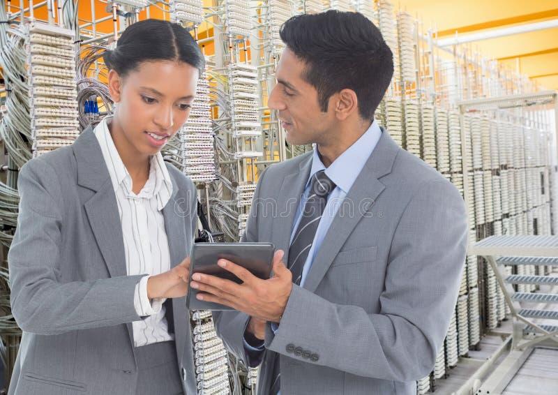 使用数字式片剂的企业同事反对数据库服务器系统在背景 免版税库存照片
