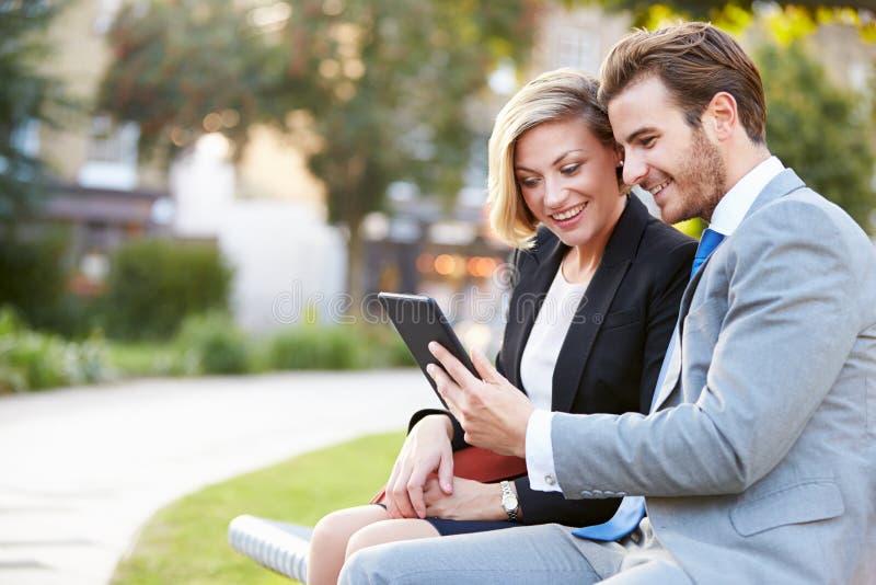 使用数字式片剂的企业夫妇在公园长椅 库存照片