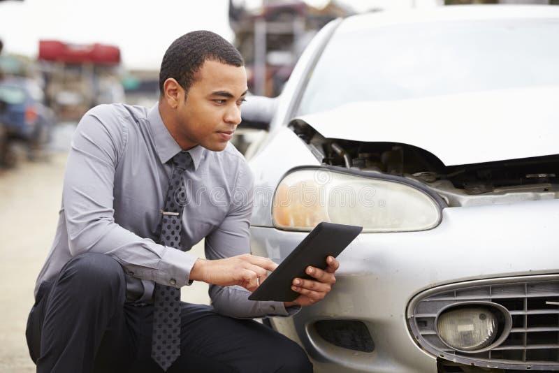 使用数字式片剂的保险赔偿估定员在汽车击毁检查 库存照片