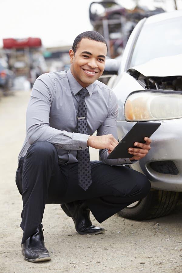 使用数字式片剂的保险赔偿估定员在汽车击毁检查 免版税库存图片