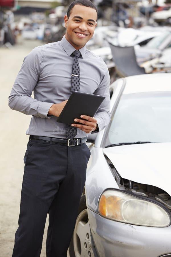使用数字式片剂的保险赔偿估定员在汽车击毁检查 免版税库存照片