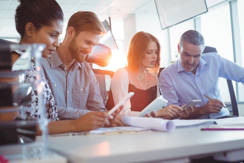 使用数字式片剂的创造性的企业同事在办公室 免版税库存图片