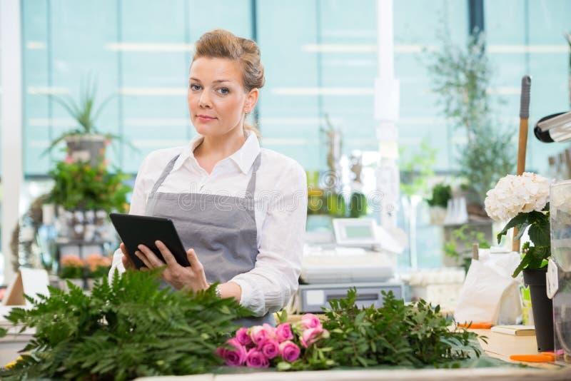 使用数字式片剂的卖花人在花店 免版税库存照片