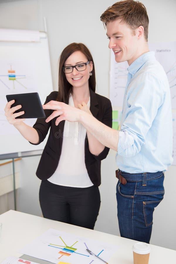 使用数字式片剂的商人和同事在书桌 库存图片