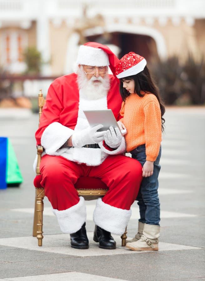 使用数字式片剂的圣诞老人和女孩 免版税库存图片