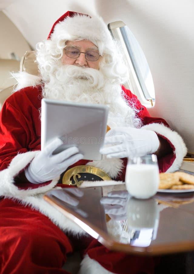 使用数字式片剂的圣诞老人在私人喷气式飞机 免版税图库摄影