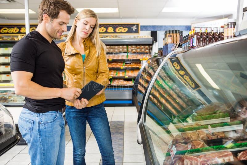 使用数字式片剂的夫妇在肉店 免版税库存照片
