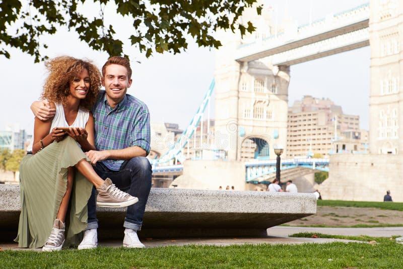 使用数字式片剂的夫妇有塔桥梁的在背景中 库存照片