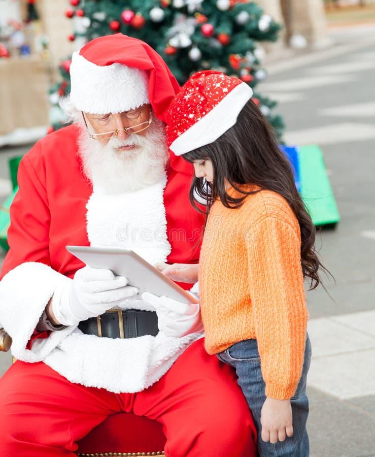 使用数字式片剂的女孩和圣诞老人 库存图片