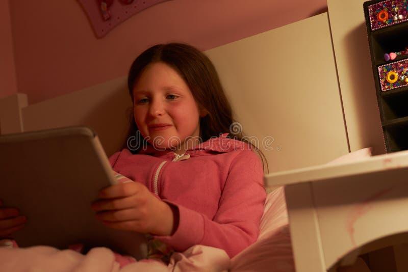 使用数字式片剂的女孩在床在晚上 库存图片