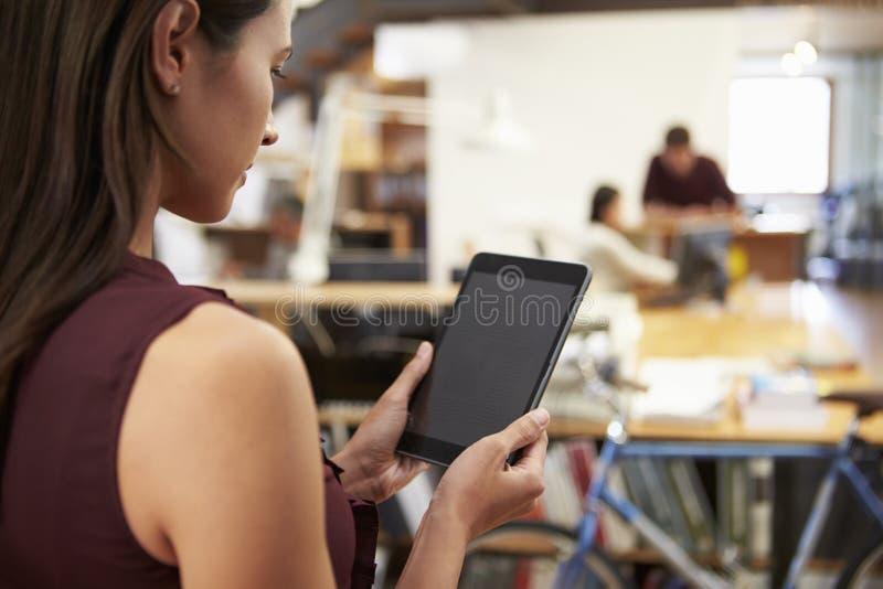 使用数字式片剂的女实业家在现代办公室 免版税库存照片