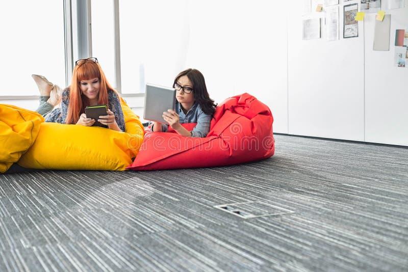 使用数字式片剂的女实业家,当放松在装豆子小布袋椅子在创造性的办公室时 免版税库存图片
