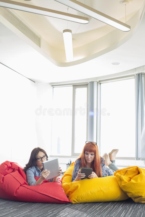 使用数字式片剂的女实业家,当放松在装豆子小布袋椅子在创造性的工作区时 免版税库存照片