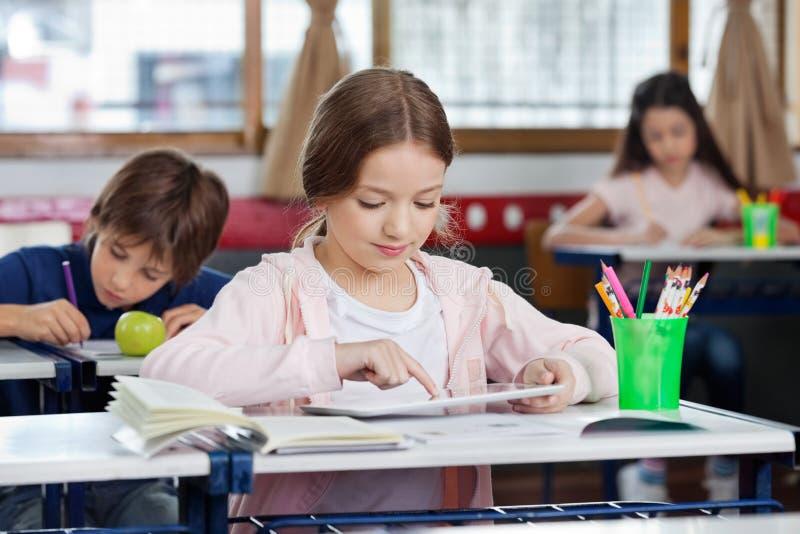 使用数字式片剂的女小学生在书桌 库存图片