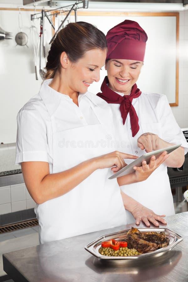 使用数字式片剂的女性厨师在厨房 免版税图库摄影