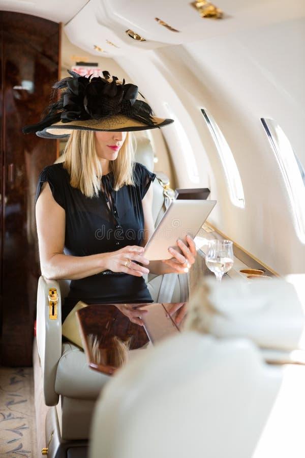 使用数字式片剂的妇女在私人喷气式飞机 免版税图库摄影