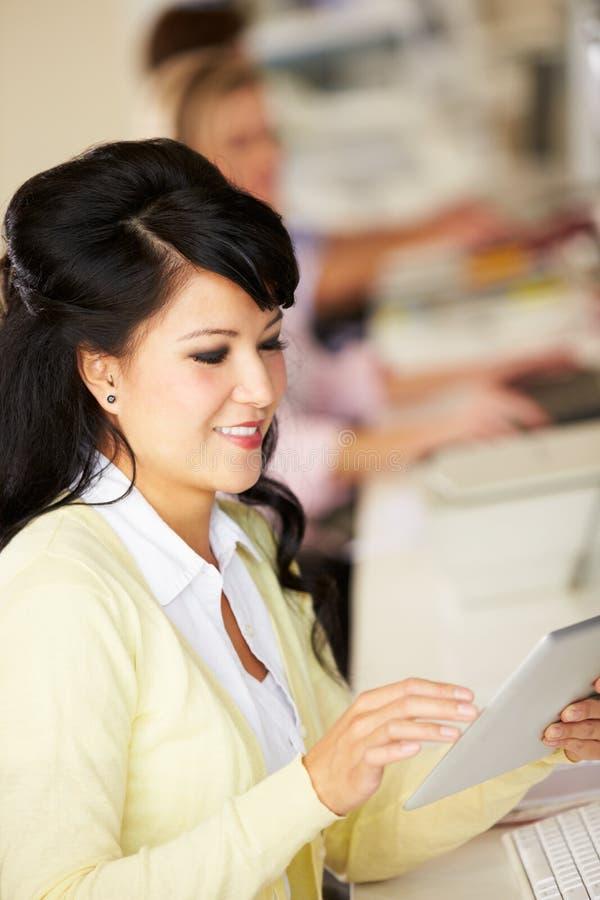 使用数字式片剂的妇女在繁忙的创造性的办公室 免版税库存图片