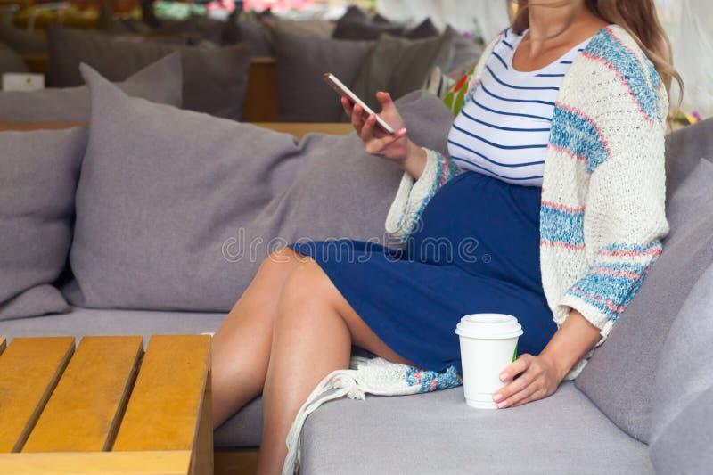使用数字式片剂的孕妇侧视图在咖啡馆 库存照片