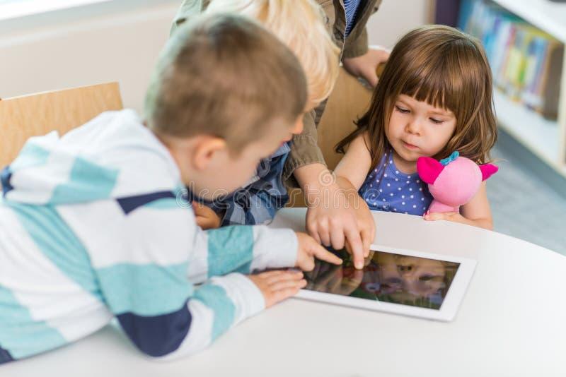 使用数字式片剂的孩子在学校图书馆 免版税库存照片