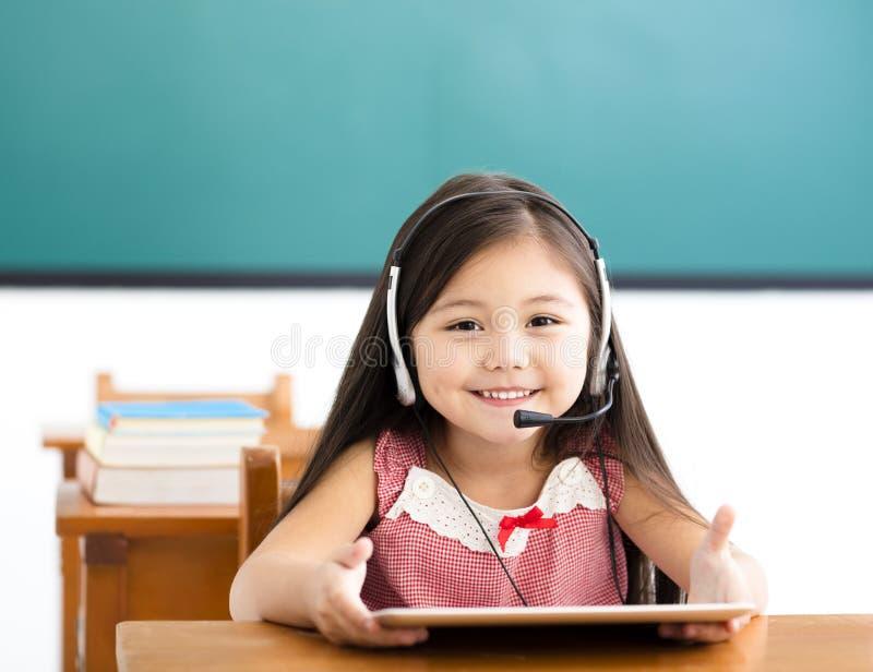 使用数字式片剂的小女孩在类 库存图片