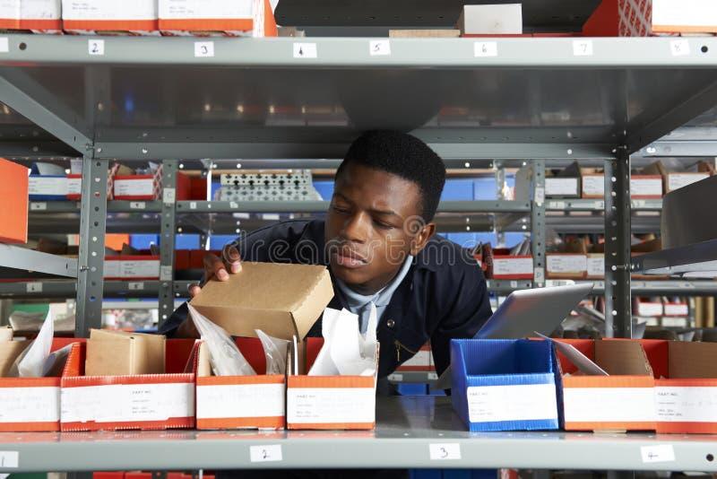 使用数字式片剂的工厂劳工在储藏室 免版税库存图片