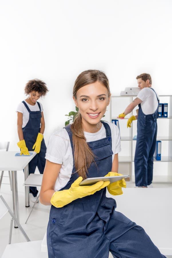 使用数字式片剂的年轻女性擦净剂和微笑对照相机,当同事时 免版税库存照片