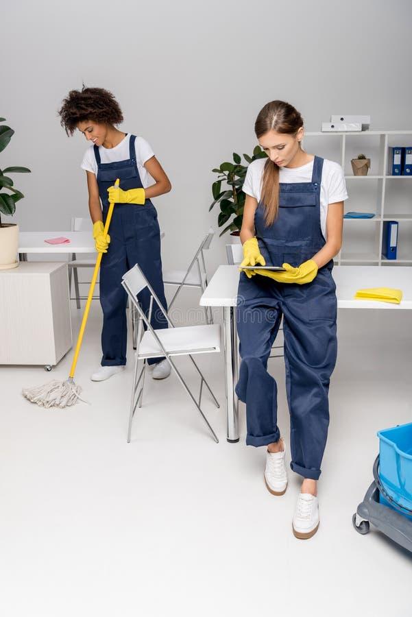 使用数字式片剂的年轻女性擦净剂,当非裔美国人的同事洗涤的地板时 免版税库存照片