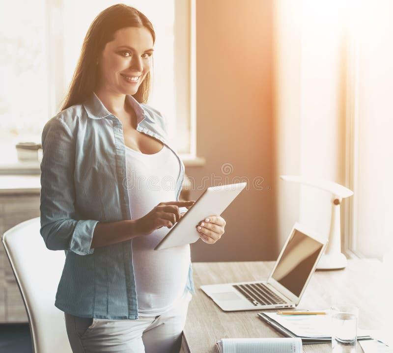 使用数字式片剂的年轻愉快的孕妇 免版税库存图片