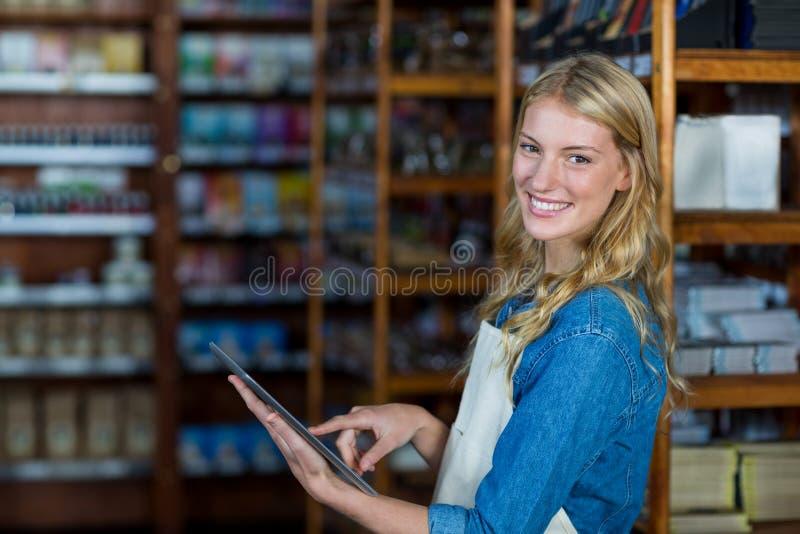 使用数字式片剂的微笑的女职工在超级市场 图库摄影