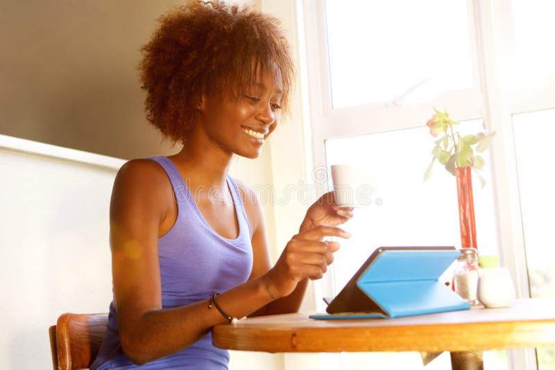 使用数字式片剂的微笑的年轻黑人妇女在咖啡馆 库存图片