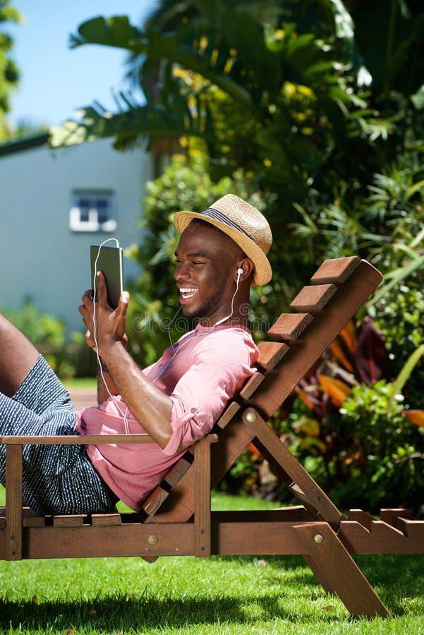 使用数字式片剂的微笑的年轻人 免版税库存照片
