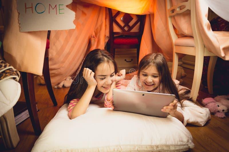 使用数字式片剂的愉快的女孩在房子由毯子制成 免版税库存图片