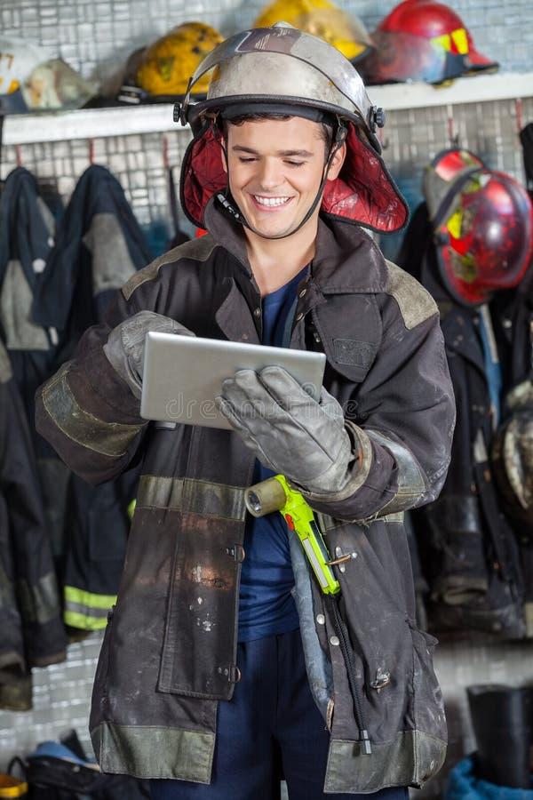 使用数字式片剂的愉快的消防员 免版税图库摄影