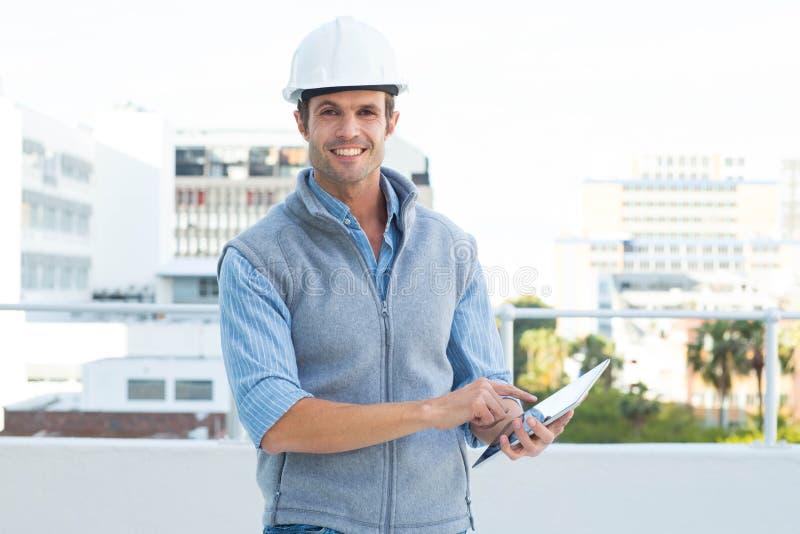 使用数字式片剂的愉快的男性建筑师 免版税库存图片